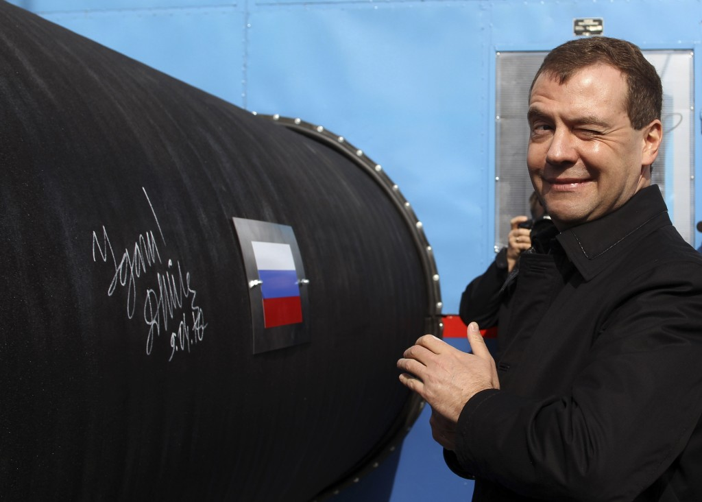 Russian President Medvedev gestures after writing 'Good Luck!' on a pipe of the Nord Stream pipeline near Russian town of Vyborg