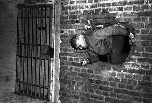Солдаты Третьей армии США ищут золотой запас Германии в соляной шахте в окрестностях Мекерса (10 апреля 1945 года). В сейф пробираются через дыру в стене, чтобы не взорваться на минах-ловушках.